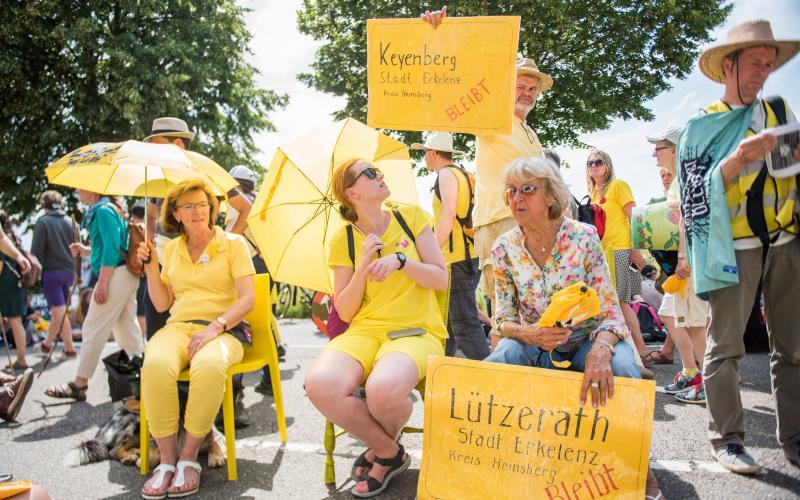 Teilnehmer*innen der symbolischen Sitzblockade 'Alle Dörfer Bleiben'